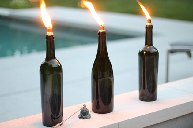 Three wine bottle tiki torches lined along a pool