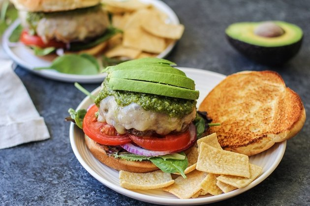 Cheeseburger with lettuce, tomato, onion, pesto sauce, and avocado