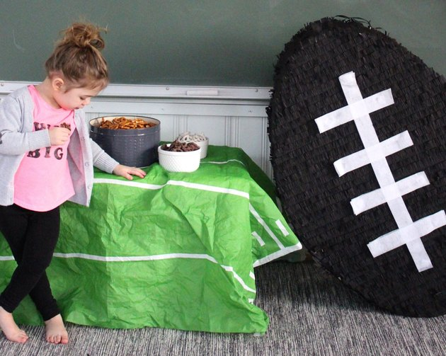 little girl next to giant football pinata