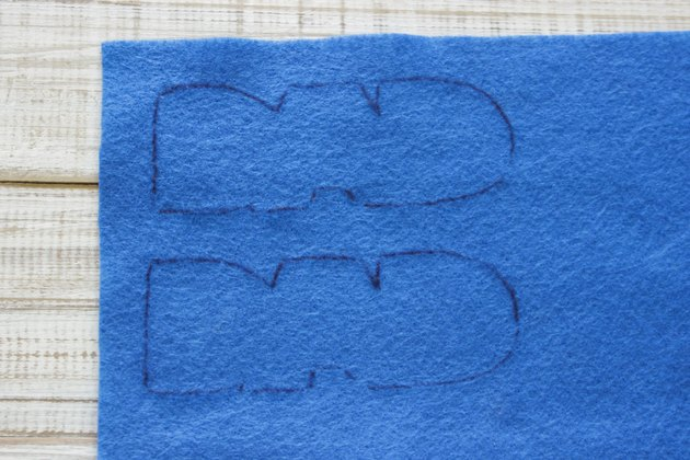 """DAD"" design traced one above the other onto blue felt."