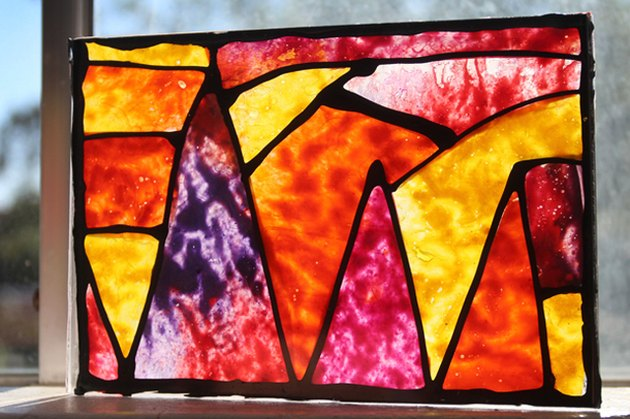 The completed, pieced version of the melted crayon stained glass, backlit by a sunny window