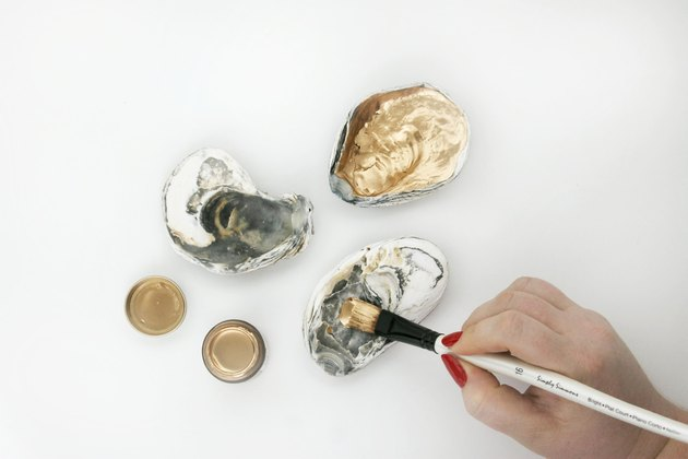 Applying paint to inside of oyster shells