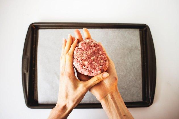 Hands shaping the beef hamburger patties.