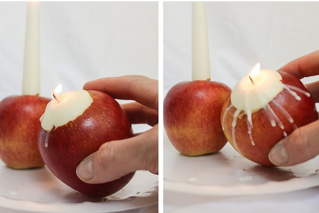 Dripping wax from tea light candle onto apple.