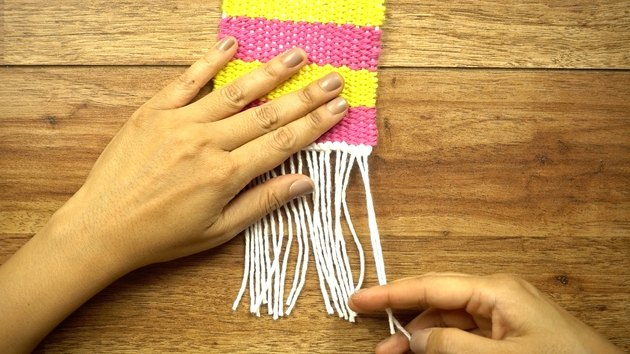 Creating a knotted fringe for DIY coasters on cardboard loom.