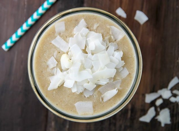 A bird's eye view of a coconut cream pie smoothie sprinkled with coconut flakes.