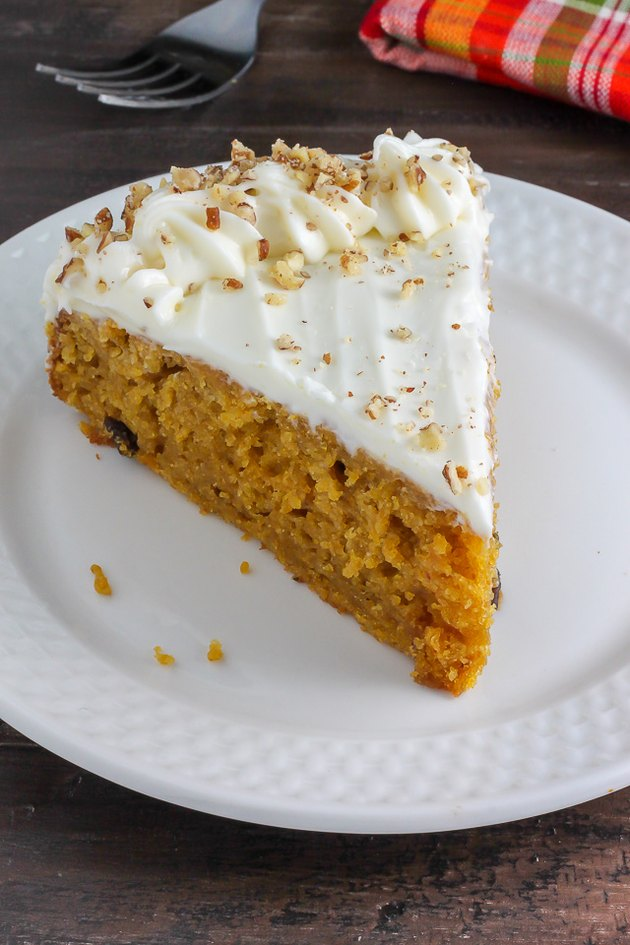 A slice of cream cheese frosted pumpkin cake ready to be served.