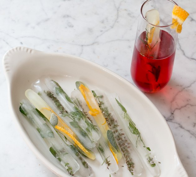 Ice cube swizzle sticks with herbs and orange peel