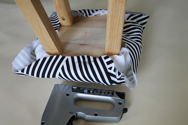 Staple the fabric to the stool.