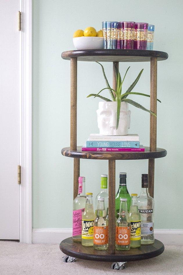Fill the three tiers of the wooden cart with bar accessories and bottles.