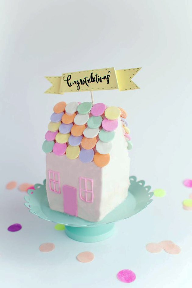 "Finished cake-shaped house with ""Congratulations"" cake topper"