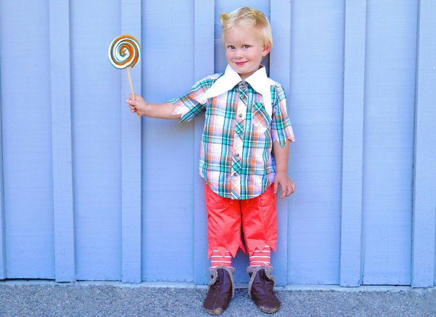 A toddler in a Munchkin costume holding a big lollipop.