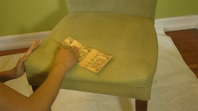 Sanding a dry coat of chalk paint on fabric upholstery.