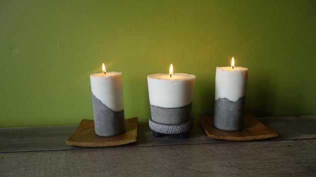 Modern DIY candles with cement base lit on table.
