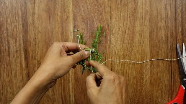 Wrapping rosemary sprig to create a mini Christmas wreath for DIY gift tag.