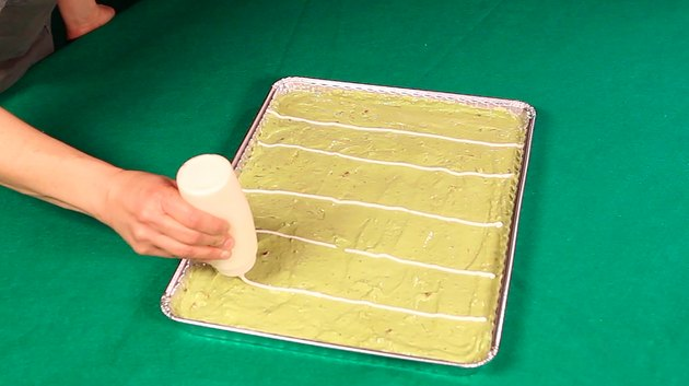 tray of guacamole with sour cream lines