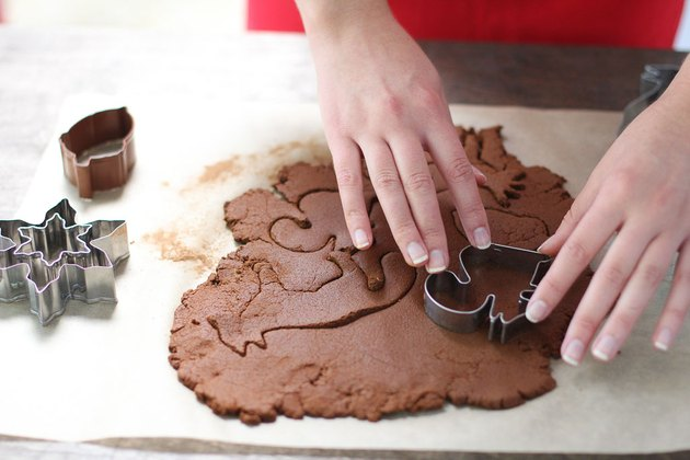 Woman using cookie cutters to form shapes from dough
