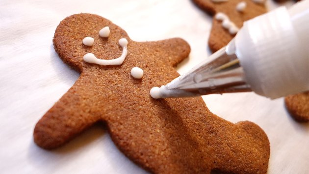 Icing a gluten-free low-carb gingerbread cookie.
