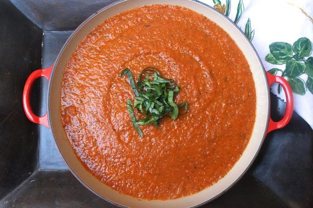 A large pot of tomato sauce topped with fresh basil