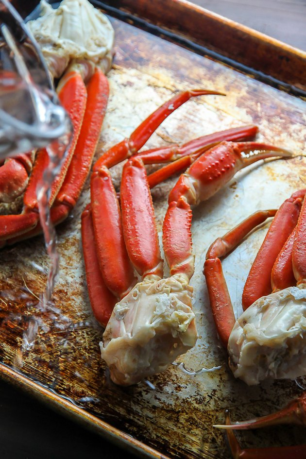 Place crab legs on a baking pan and pour water in.