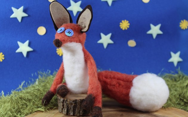 Orange wool felted fox in front of a starry background.