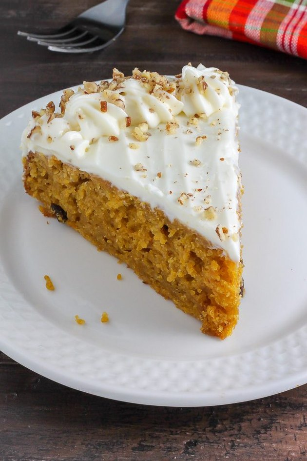 A slice of fluffy pumpkin cake frosted with a cream cheese mixture.