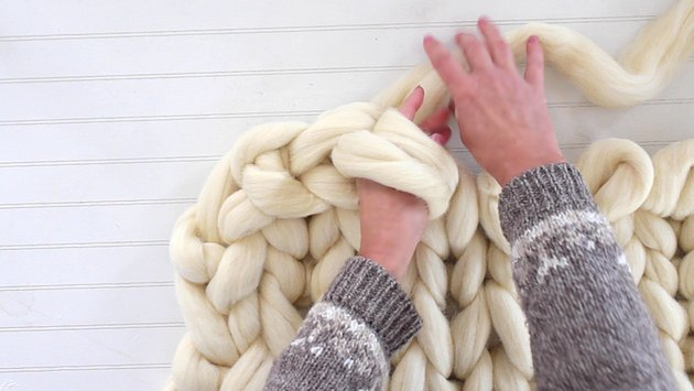 reach hand through the two loops and grab the yarn