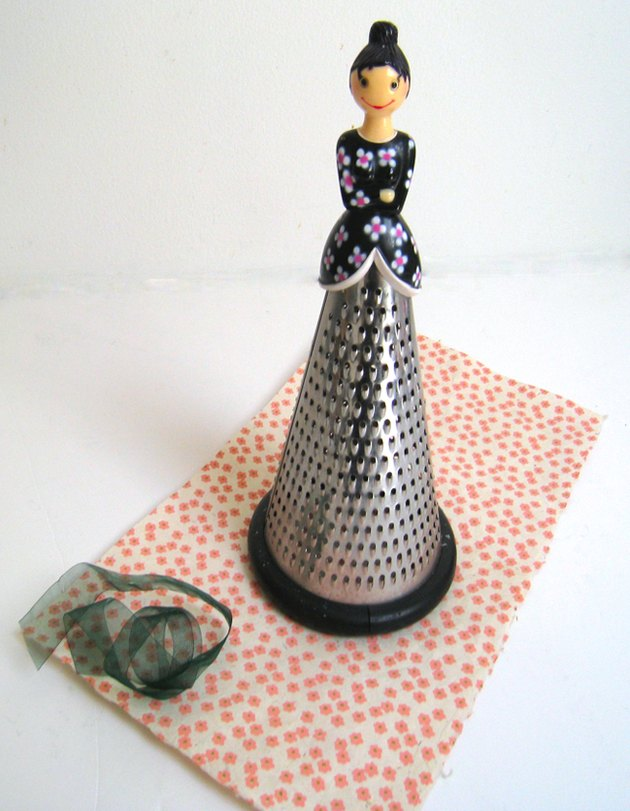 cheese grater with lady's doll head on top