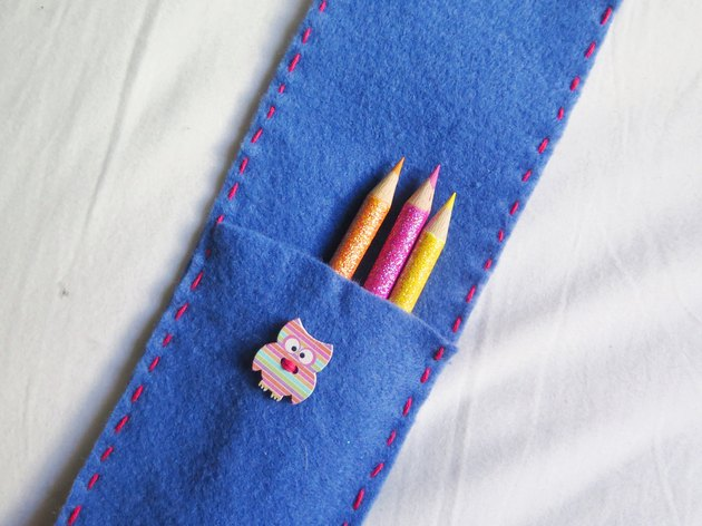 Colored pencils placed into the felt case.