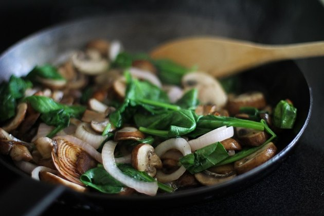 Sauteed onion, mushrooms and spinach in a frying pan.