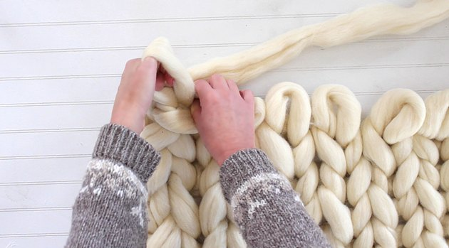 pull yarn through the two loops to create another 4-inch loop