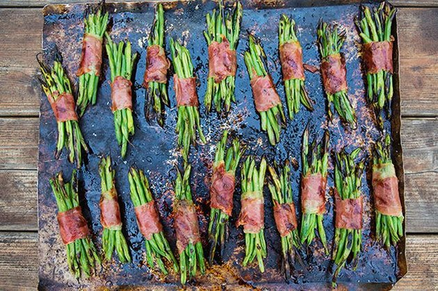 Several prosciutto and green bean bundles on a cookie sheet