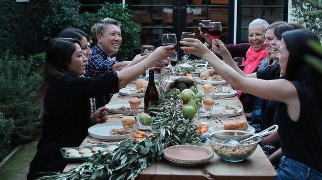 people toasting with wine glasses around a table