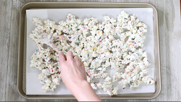 spreading rainbow popcorn on baking tray