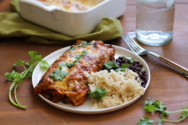 Plate of vegetarian enchiladas with beans and rice.