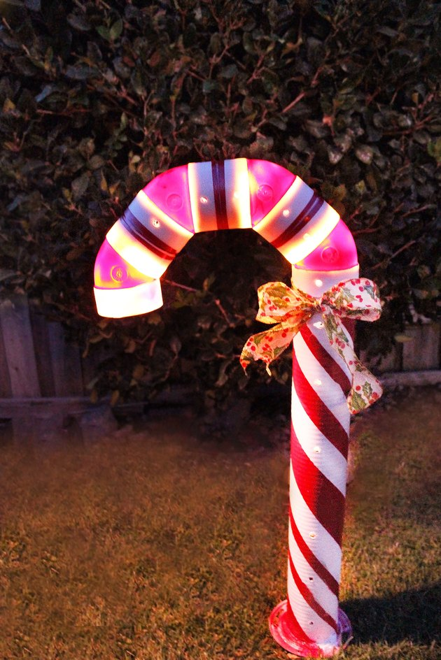 lighted candy cane decoration outside at night
