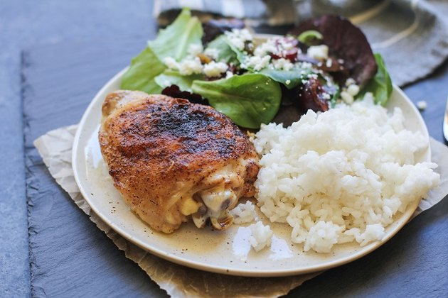 Baked chicken thigh on a plate with rice and salad