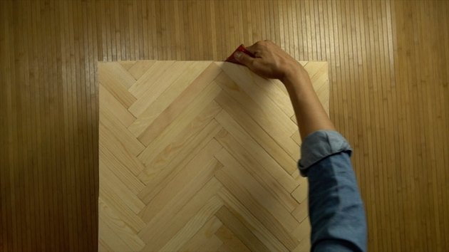 Sanding edges of DIY herringbone pattern tabletop using paint sticks.