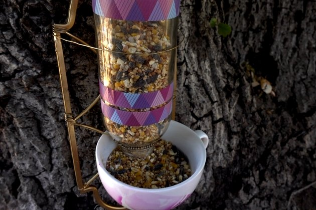 DIY bird feeder made from wrought iron candle sconce and teacup.