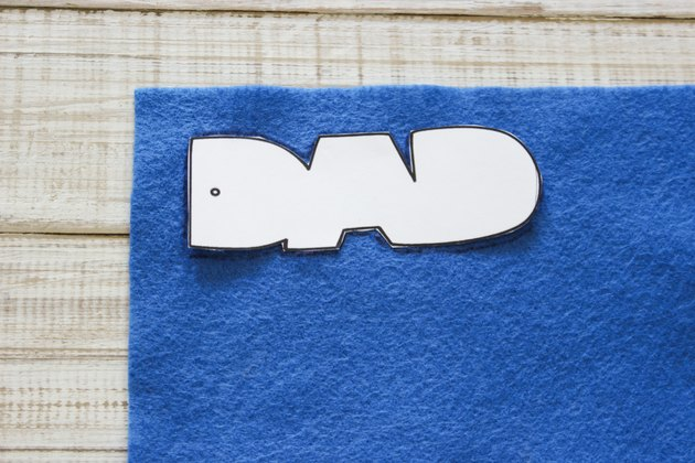 """DAD"" cut out template placed on top of blue felt."
