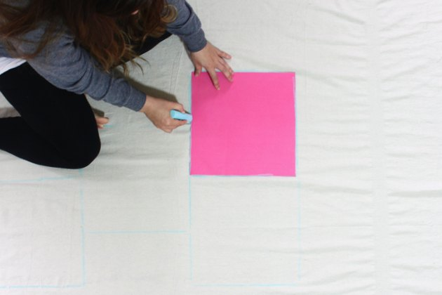 woman marking a drop cloth with chalk
