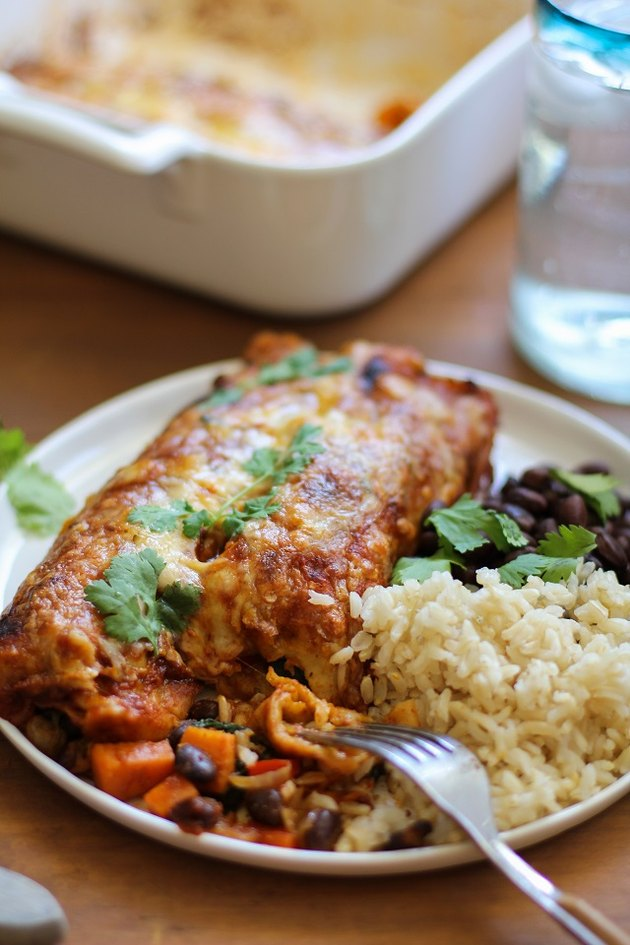 Plate with two vegetarian enchiladas, black beans and rice.
