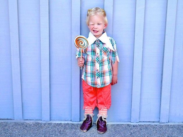 Little boy in costume holding a big lollipop.