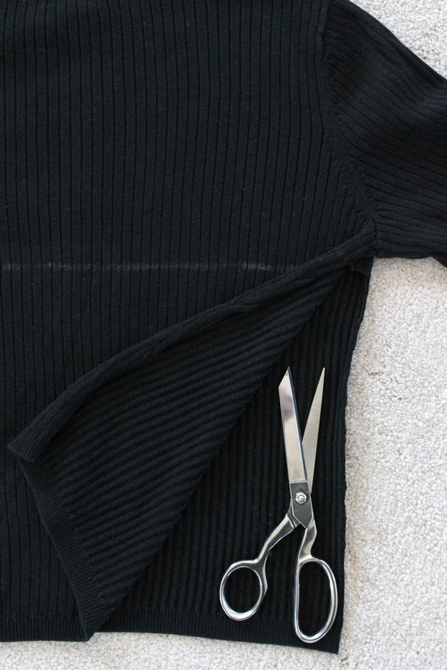 Cut the side seams of the sweater open up to the mark.