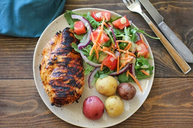 Grilled chicken on a plate with salad and potatoes