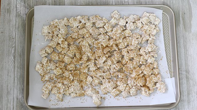 golden chex cereal spread onto baking tray