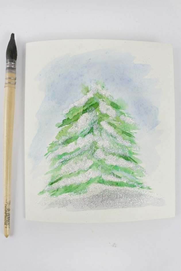 A watercolor of a snow-topped tree.