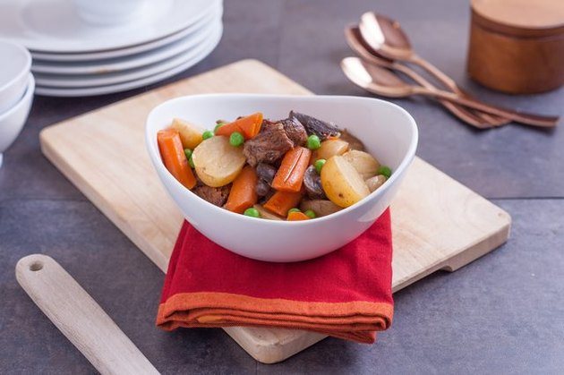 A white bowl full of hearty beef and vegetable stew