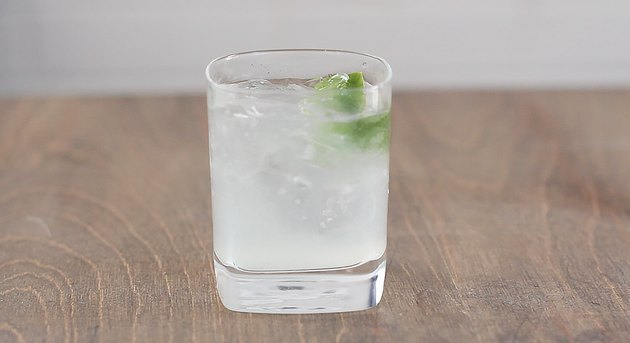 gin and tonic with lime wedge garnish