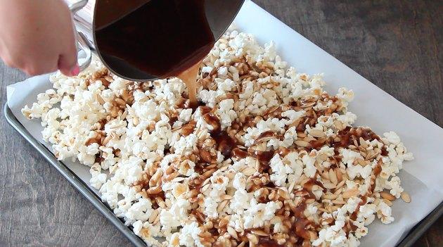 Pouring caramel sauce over popcorn mix.